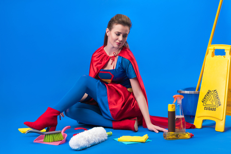 woman in superhero costume with cleaning supplies around isolated on blue