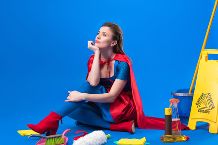 pensive woman in superhero costume with cleaning supplies around isolated on blue