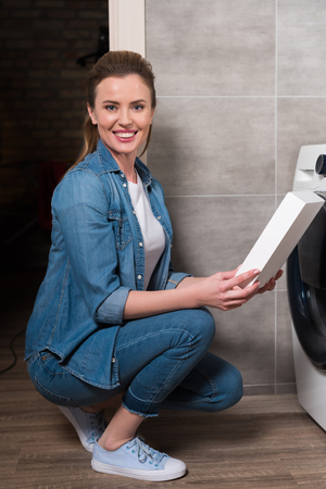smiling housewife with washing powder in hands doing laundry at home