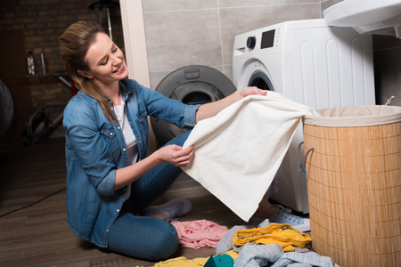 housewife taking clothing to put it into washing machine at home