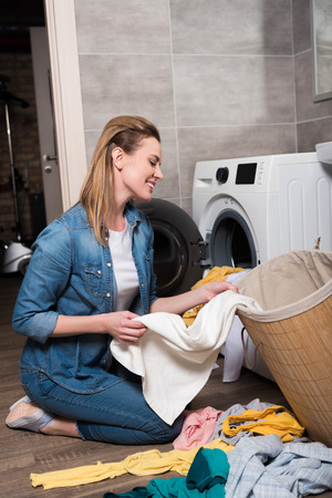 smiling housewife taking clothing to put it into washing machine at home