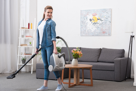 smiling woman with vacuum cleaner in hands looking away 스톡 콘텐츠