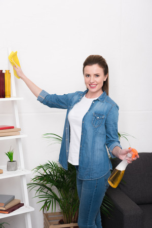 portrait of attractive woman with rag and disinfect spray cleaning home