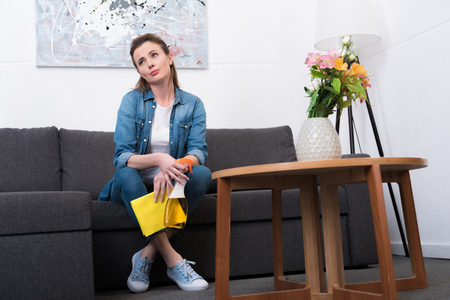 tired woman with cleaning supplies in hands resting on sofa at home