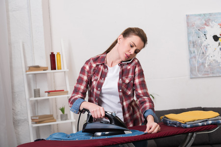 portrait of woman talking on smartphone while ironing clothes at home