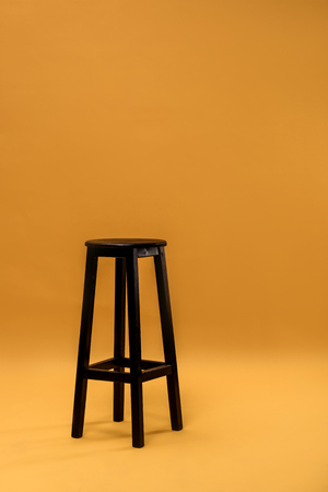 Dark wooden bar stool on orange background