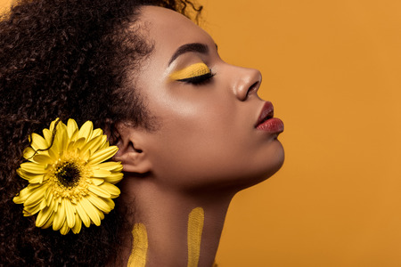 Stylish african american woman with artistic make-up and gerbera in hair dreaming isolated on orange background Foto de archivo