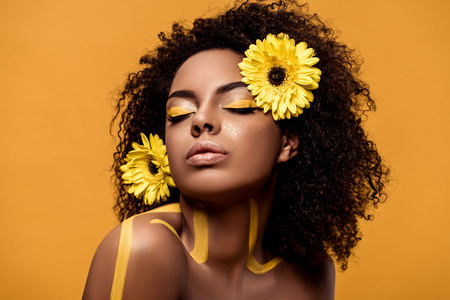 Young sensual african american woman with artistic make-up and gerbera in hair isolated on orange background