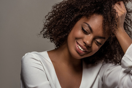 Young sensual african american woman in white shirt rests on the hand isolated on grey background