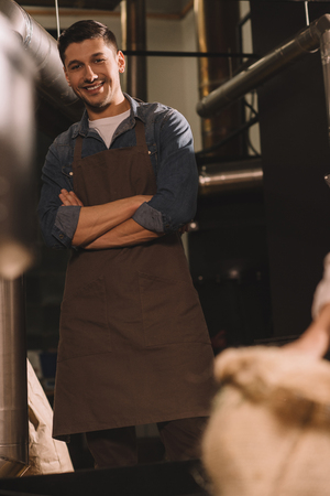 portrait of cheerful worker in apron with arms crossed looking at camera