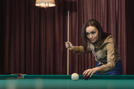 pretty young girl playing in pool at bar