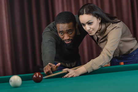 young attractive multiethnic man and woman playing in pool at bar