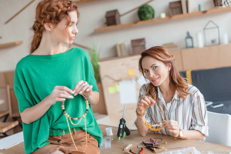 young women with handmade necklaces at workshop Stock Photo