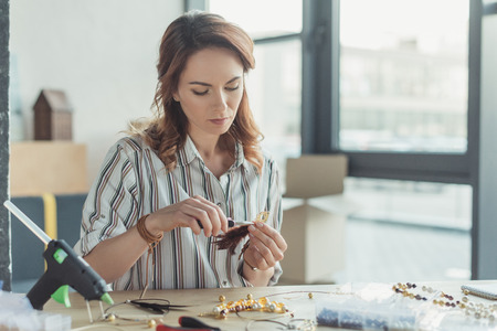 concentrated young woman making accessories in workshop Stock Photo