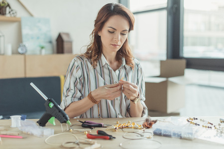 concentrated young woman making accessories of beads in workshop Stock Photo