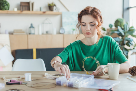 young woman making necklaces in handmade workshop Stock Photo