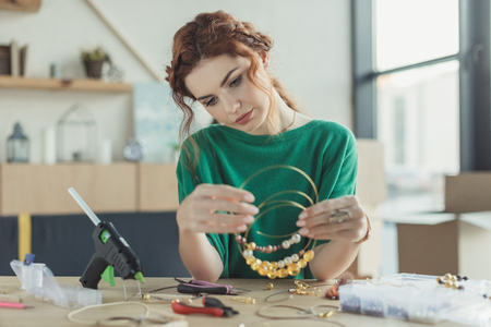 young woman holding handmade necklaces in workshop Stock Photo