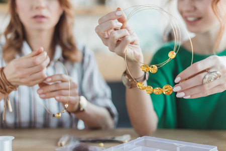 young concentrated women making chaplets in handmade workshop