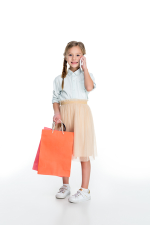 smiling child with shopping bags in hand talking on smartphone isolated on white Stock Photo