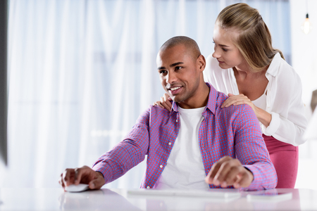 smiling caucasian girlfriend hugging african american boyfriend sitting at computer