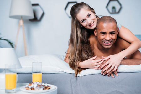 smiling multicultural couple lying on bed and looking at camera