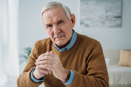 Senior thoughtful man sitting by the desk in light room Stok Fotoğraf