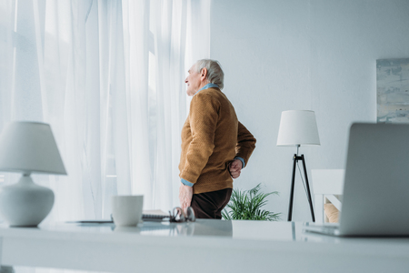 Senior man working in office suffering from back pain