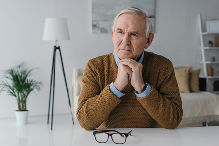 Senior thoughtful man sitting by the desk in light room 스톡 콘텐츠