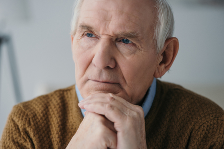 Senior thoughtful man leaning on hands in light room 스톡 콘텐츠