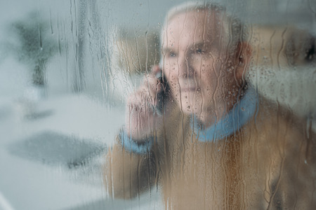 Behind the rainy glass view of senior disturbed man making a phone call