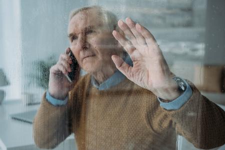 Achter de glazen weergave van senior man die een telefoongesprek voert