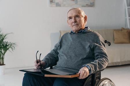 Senior man in wheelchair holding old photo album