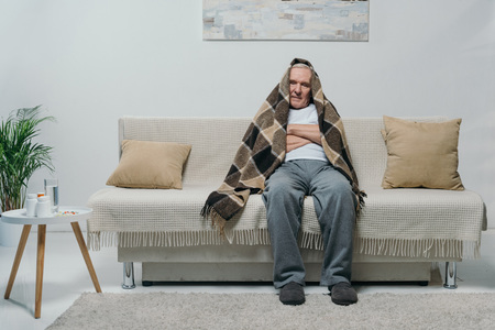 Senior chilled man covered in plaid sitting on sofa 写真素材