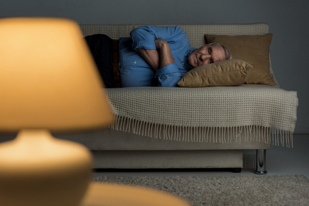 Senior tired man sleeps on a sofa in living room