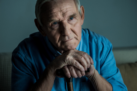 Tired senior man leans on a cane while sitting on sofa 스톡 콘텐츠