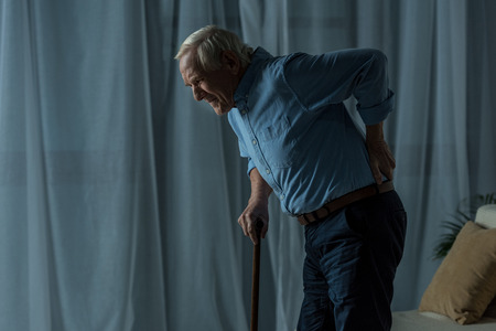 Senior man suffering from back pain leans on a cane