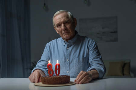 Senior lonely man celebrating 80 anniversary with cake and burning number candles