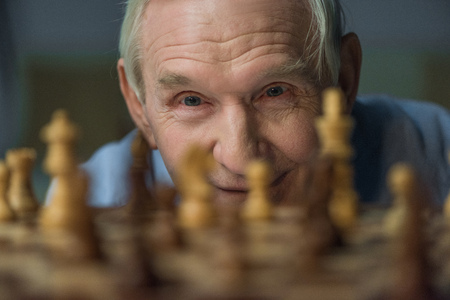 Senior confident man looks at the chess board