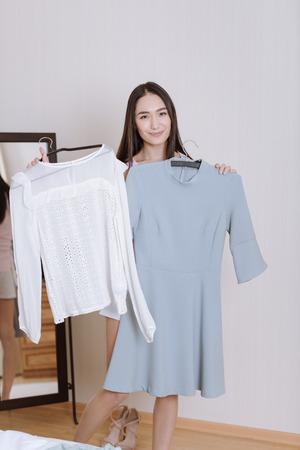 beautiful asian girl choosing between shirt and dress