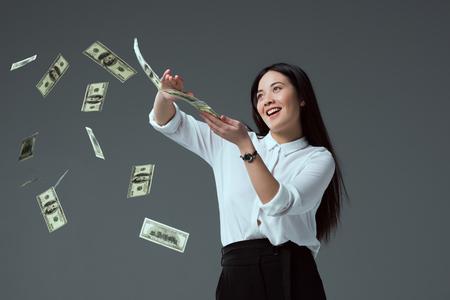 Glimlachend Aziatisch meisje dat dollarbankbiljetten gooit die op grijs worden geïsoleerd