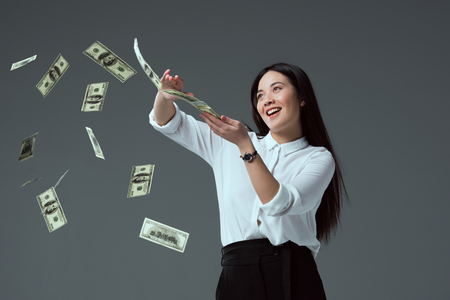 smiling asian girl throwing dollar banknotes isolated on grey