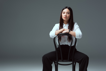 beautiful asian girl sitting on chair and looking at camera on grey