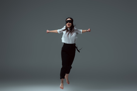 young barefoot woman in black blindfold jumping with open mouth on grey