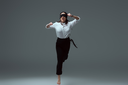 aggressive young barefoot woman in black blindfold jumping with open mouth on grey