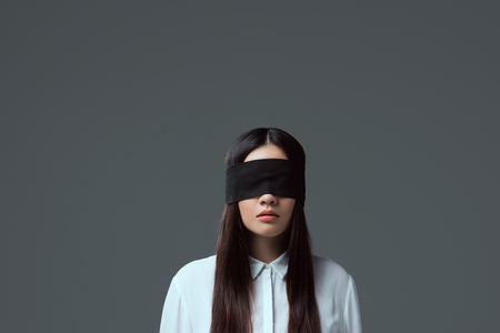 brunette girl wearing black blindfold isolated on grey