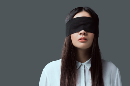 young woman wearing black blindfold isolated on grey Stockfoto