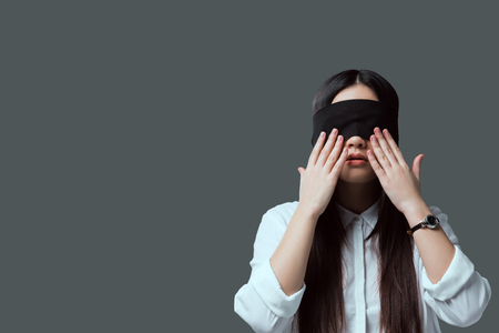 young woman in black blindfold touching face with hands isolated on grey