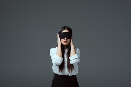 young blindfolded woman closing ears isolated on grey Stockfoto