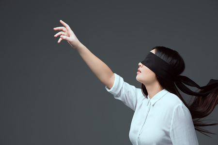 side view of young woman wearing black blindfold and raising hand isolated on grey Stockfoto