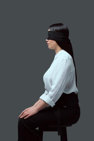 zijaanzicht van jonge geblinddoekte vrouw zittend op een stoel geïsoleerd op grijs
